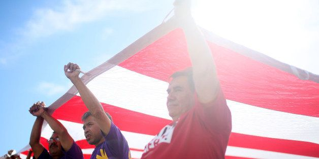 LOS ANGELES, CA - MAY 1:  Protesters chant while carrying an American flag during a May Day rally on Friday, May 1, 2015 in d