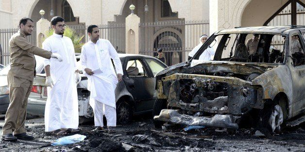 Saudi security forces and forensic personnel inspect the site of a suicide bombing that targeted the Shiite Al-Anoud mosque i