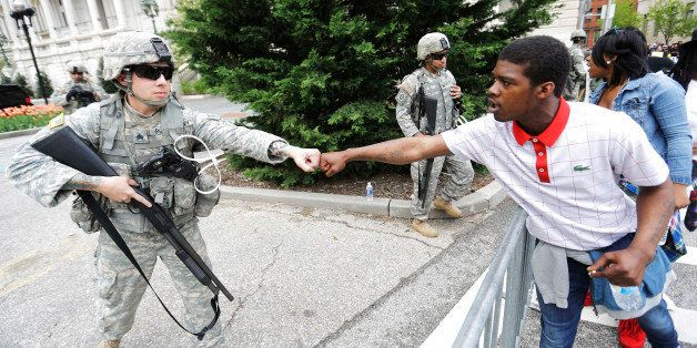 Brandon Payton, right, of Baltimore, fist-bumps a National Guardsman standing outside of City Hall as protesters march by to