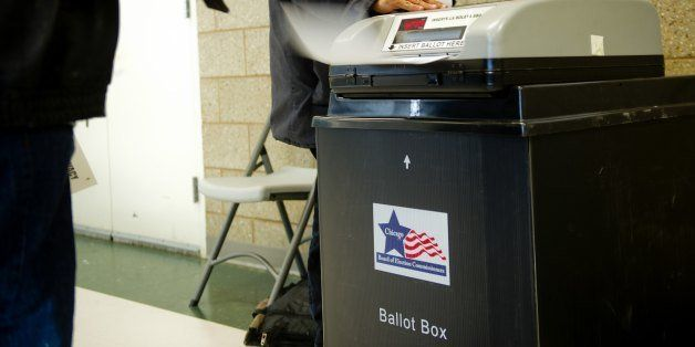 A voter slides his ballot into the ballot box at a polling place on the Northside of Chicago, Illinois on November 6, 2012. C