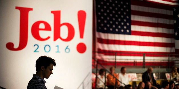 Campaign intern Jack Nalen hands out signs at Miami Dade College in Miami, Monday, June 15, 2015, before former Florida Gov. Jeb Bush is expected to formally join the race for president with a speech. (AP Photo/David Goldman)