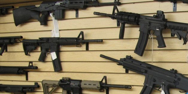 Frank Loane, owner of Pasadena Pawn and Gun, stands in front of a wall of assault rifles at his store in Pasadena, Md., on Th