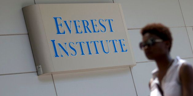 This photo taken July 8, 2014 shows a person walking past an Everest Institute sign in a office building in Silver Spring, Md