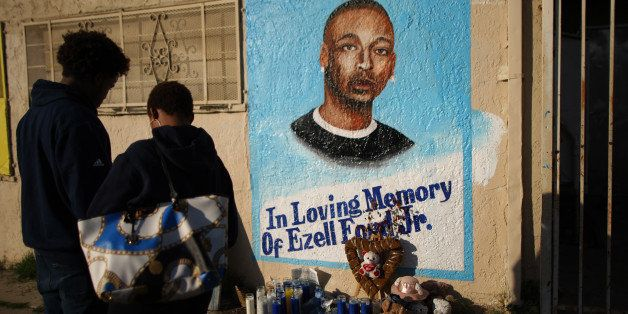 LOS ANGELES, CA - DECEMBER 29:  People look at a mural of Ezell Ford, a 25-year-old mentally ill black man, at the site where