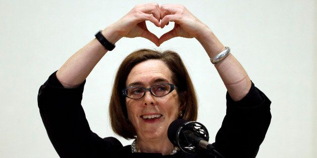 "Oregon Gov. Kate Brown forms a heart with her hands as she says ""I love Oregon"" during her State of the State address in Port"