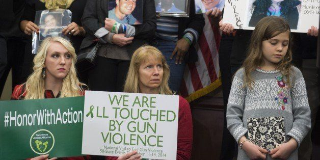 Relatives of victims of gun violence and gun violence prevention advocates hold up photos of victims during a press conferenc