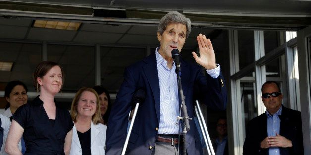 Secretary of State John Kerry waves after speaking to media as he is discharged from Massachusetts General Hospital Friday, J