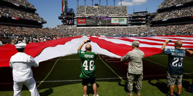 PHILADELPHIA, PA - SEPTEMBER 07: Members of the US Armed Forces and season ticket holders hold a large American Flag along wi