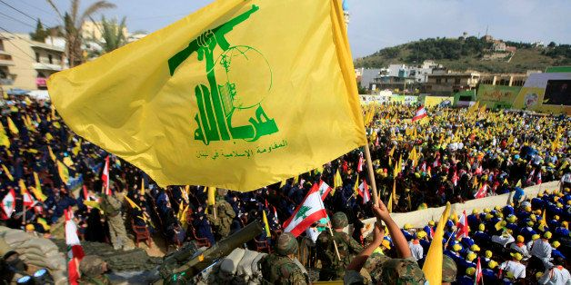 "A Hezbollah fighter waves its flag as other fighters stand guard during a rally commemorating ""Liberation Day,"" which marks t"