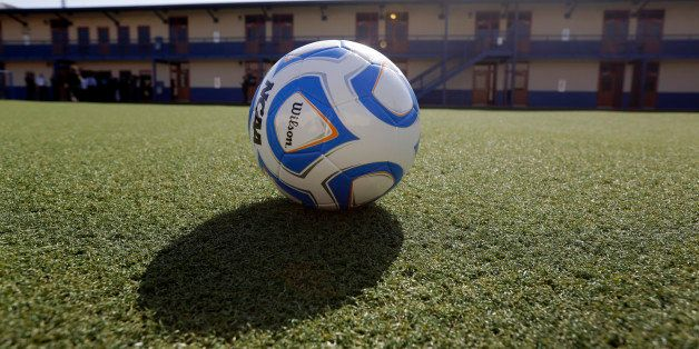 A soccer ball rests on an artificial turf soccer field in a courtyard at the Karnes County Residential Center, Thursday, July