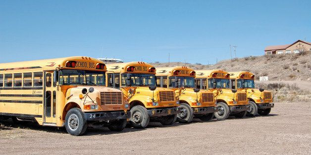 The quintessential yellow schoolbuses of America, lined up back at their desert depot.