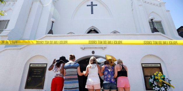 A group of women pray together at a make-shift memorial on the sidewalk in front of the Emanuel AME Church, Thursday, June 18
