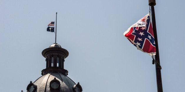 COLUMBIA, SC - JUNE 18:  The South Carolina and American flags fly at half mast as the Confederate flag unfurls below at the