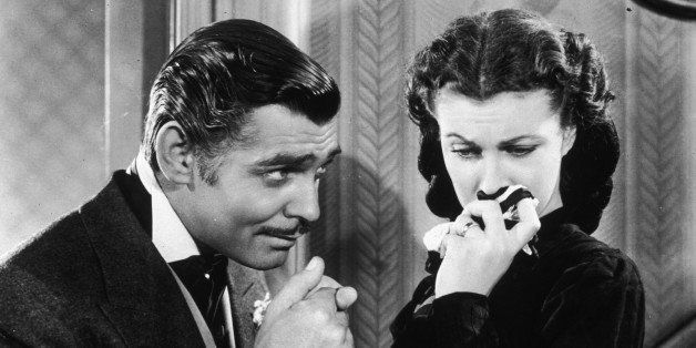 American actor Clark Gable (1901 - 1960) in his role as Rhett Butler kissing the hand of a tearful Scarlett O'Hara, played by