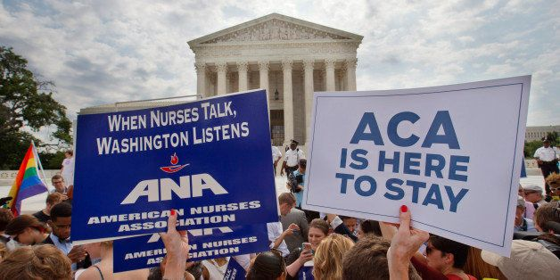 Supporters of the Affordable Care Act hold up signs as the opinion for health care is reported outside of the Supreme Court i