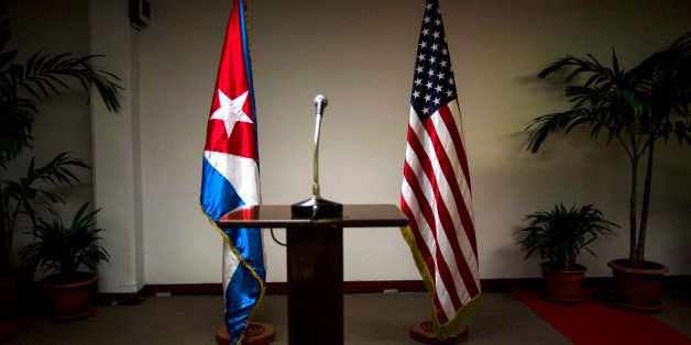 FILE - In this Jan. 22, 2015 file photo, a Cuban and U.S. flag stand before the start of a press conference on the sidelines