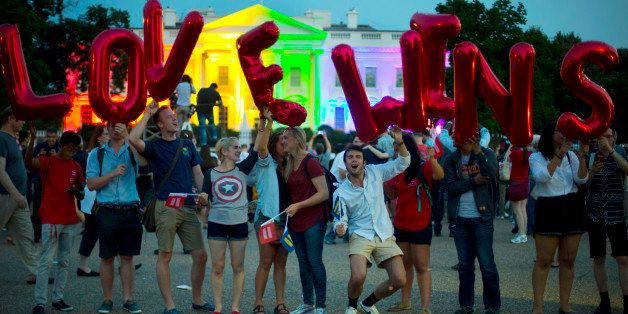 """Same-sex marriage supporters hold up balloons that spell the words """"love wins"""" as they stand in front of the White House, whi"""