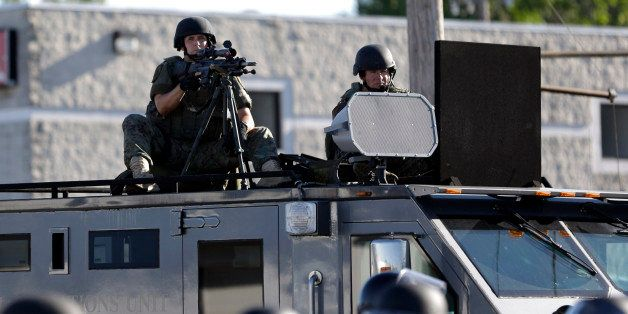 FILE - In this Aug. 9, 2014 file photo, a police tactical team moves in to disperse a group of protesters in Ferguson, Mo. th