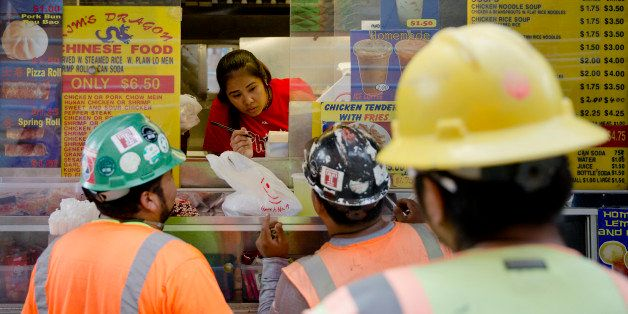 Construction workers order lunch from a food truck vender Tuesday, Sept. 16, 2014, in Philadelphia. (AP Photo/Matt Rourke)