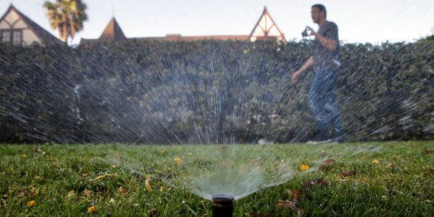 In this Friday, June 5, 2015, photo, Tony Corcoran records sprinklers watering the lawn in front of a house in Beverly Hills,