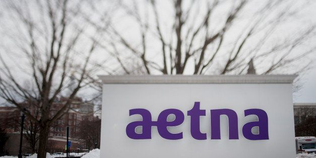 Snow covers the ground around Aetna Inc. signage displayed outside of the company's corporate headquarters in this photo take