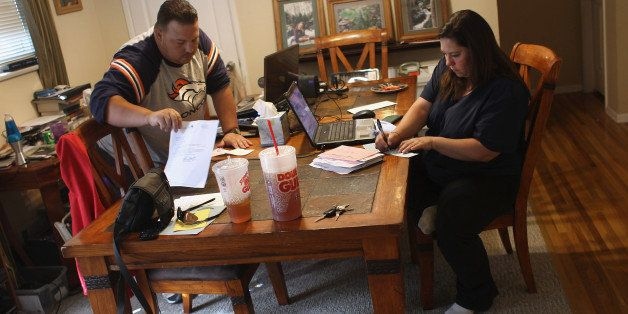 LAKEWOOD, CO - OCTOBER 07:  Iraq War veteran Brad Hammond (L) helps as his wife Dani Hammond writes checks to pay household b