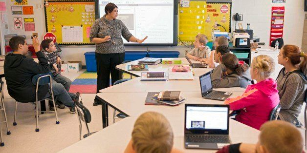 In this photo taken Feb. 12, 2015, sixth grade teacher Carrie Young guides her students through an exercise on their laptops