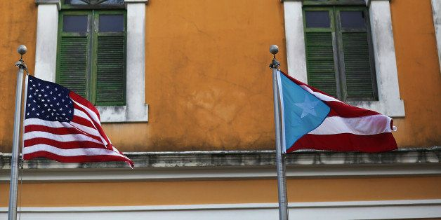 SAN JUAN, PUERTO RICO - JUNE 30:  An American flag and Puerto Rican flag fly next to each other in Old San Juan a day after t
