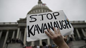 A demonstrator opposed to Supreme Court nominee Brett Kavanaugh holds a 'Stop Kavanaugh' sign on the East Front of the U.S Capitol in Washington, D.C., U.S., on Saturday, Oct. 6, 2018. The Senate is set to hold a final vote to confirm Kavanaugh Saturday, letting him take the bench when the court hears its next arguments on Tuesday. Photographer: Andrew Harrer/Bloomberg via Getty Images