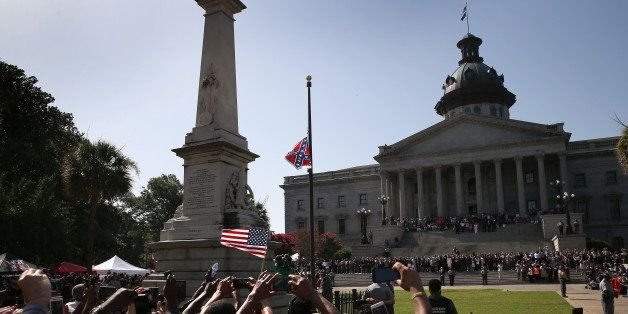 COLUMBIA, SC - JULY 10:  A crowd cheers as a South Carolina state police honor guard lowers the Confederate flag from the Sta