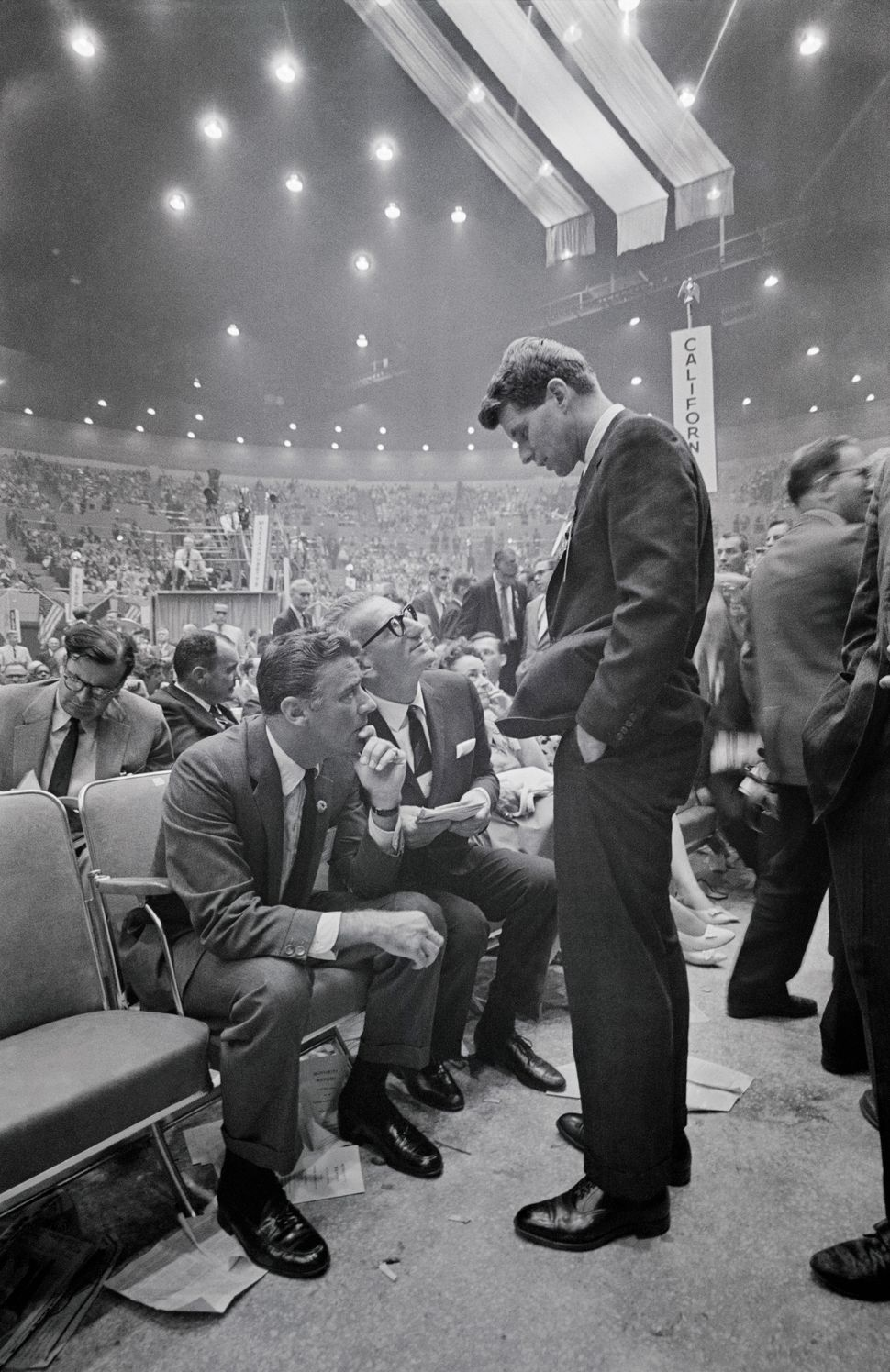 Robert F. Kennedy (standing), then-campaign manager for his brother, John F. Kennedy, chats here with actor Peter Lawford (se
