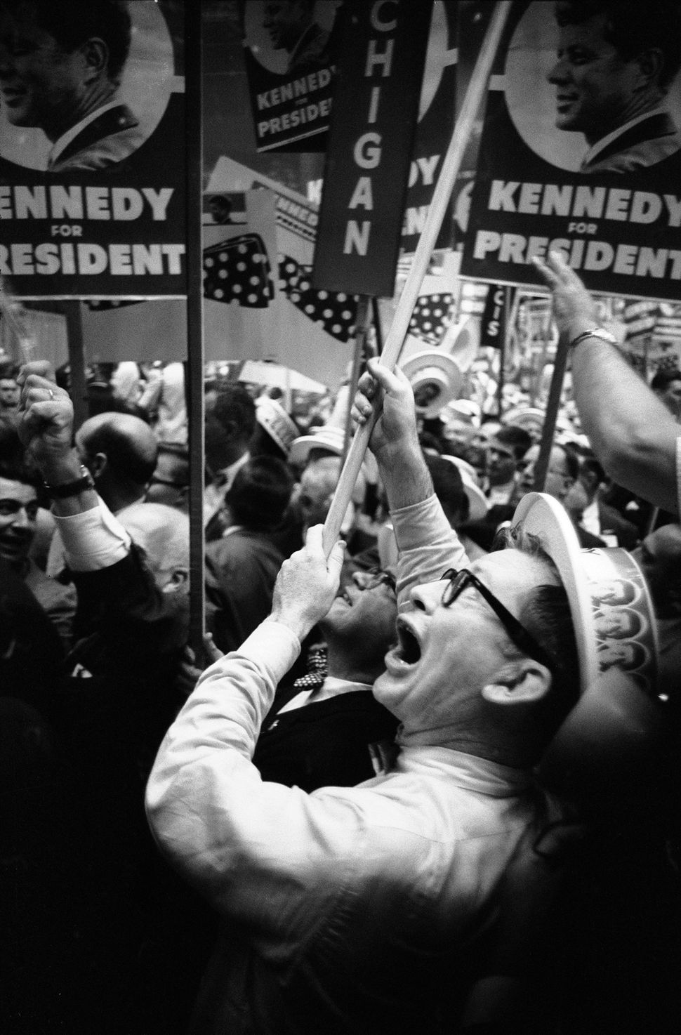 At the Democratic National Convention, delegates cheer in support of presidential candidate John F. Kennedy.