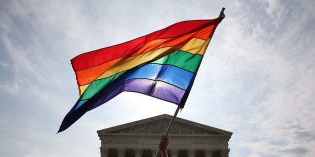 WASHINGTON, DC - JUNE 25: A gay marriage waves a flag in front of the Supreme Court Building June 25, 2015 in Washington, DC.