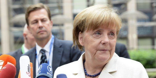German Chancellor Angela Merkel talks to the media as he arrives for a meeting of the leaders of the 19 countries that use th