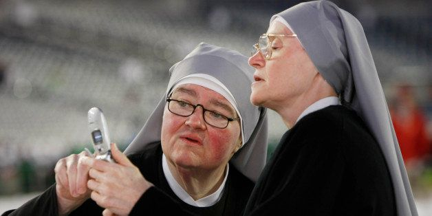 Little Sisters of the Poor Sister Kathleen Marie, right, shows Sister Ann Marguerite how to use their communal cell phone in