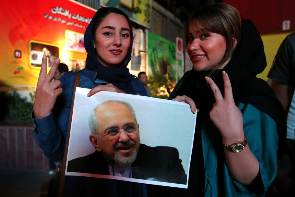 Iranian women hold a portrait of Iranian Foreign Minister Mohammad Javad Zarif and flash the v sign for victory during celebr