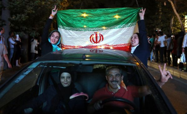 Iranian women wave the national flag during celebration in northern Tehran on July 14, 2015, after Iran's nuclear negotiating