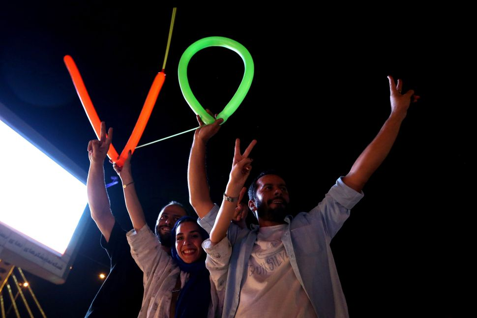 Iranians flash the V sign for victory during celebration in northern Tehran on July 14, 2015, after Iran's nuclear negotiatin