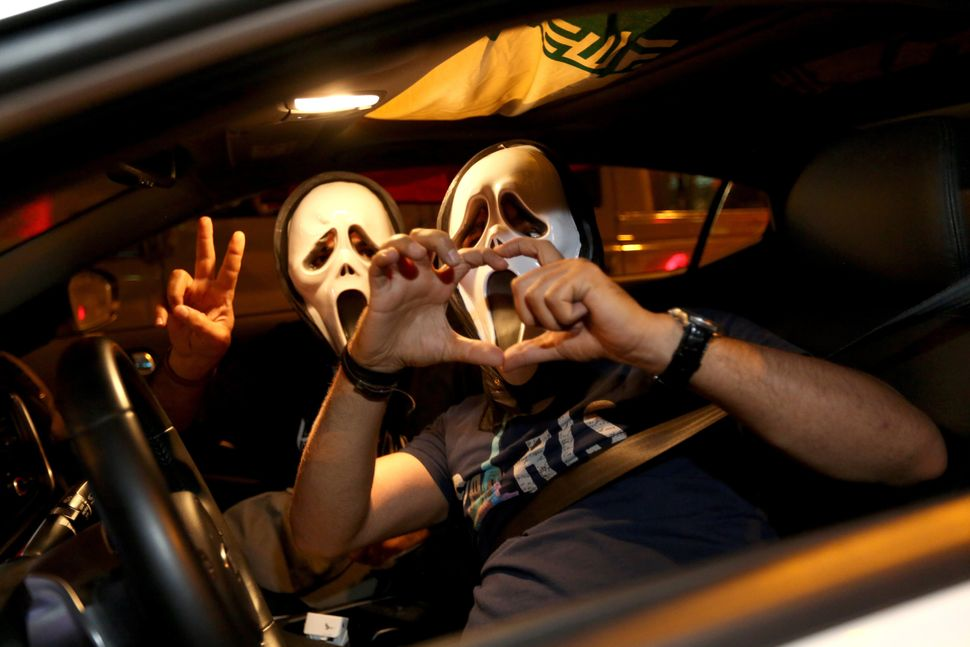 Iranian wearing the mask of 'The Scream' move flash the v sign for victory and a heart during celebration in northern Tehran