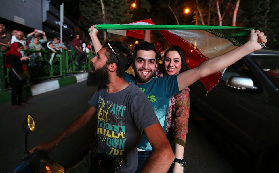 Iranian wave the national flag during celebration in northern Tehran on July 14, 2015, after Iran's nuclear negotiating team