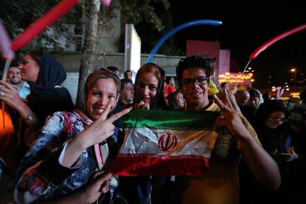Iranian women wave the national flag and flash the v sign for victory during celebration in northern Tehran on July 14, 2015,