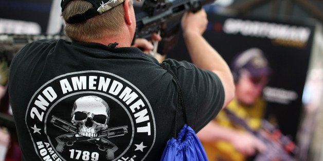 HOUSTON, TX - MAY 05:  An attendee wears a 2nd amendment shirt while inspecting an assault rifle during the 2013 NRA Annual M