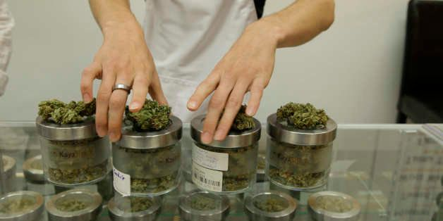 In this Friday, June 26, 2015 photo, an employee at the medical marijuana dispensary Kaya Shack displays different types of m
