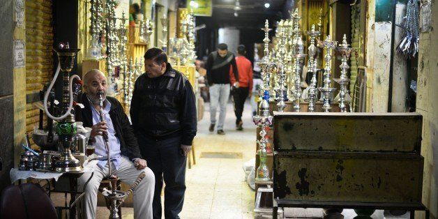 An Egyptian man smokes a water pipe not far from al-Moez street in Cairos Khan al-Khalili district on February 20, 2015. Al-M