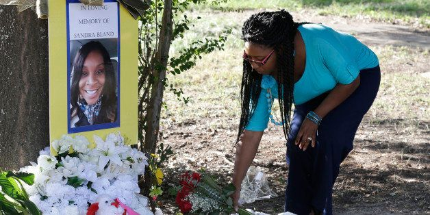 Jeanette Williams places a bouquet of roses at a memorial for Sandra Bland near Prairie View A&M University, Tuesday, Jul