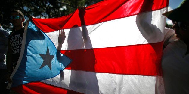 People march holding a Puerto Rican national flag in San Juan, Puerto Rico, Saturday, Nov. 23, 2013. Puerto Ricans marched th