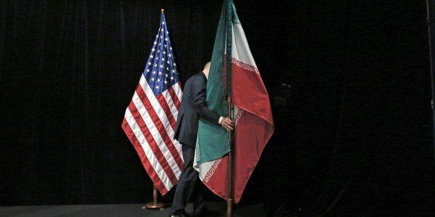 A staff removes the Iranian flag from the stage after a group picture with foreign ministers and representatives of Unites St