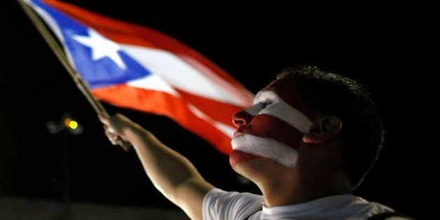 A Puerto Rican fan waves his country's flag as he watches a live telecast of the World Baseball Classic championship game bet