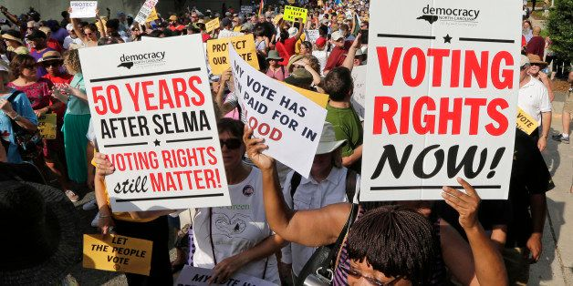 Demonstrators march through the streets of Winston-Salem, N.C., Monday, July 13, 2015, after the beginning of a federal votin