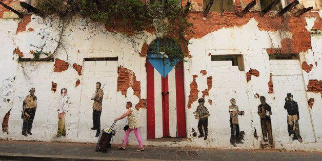 OLD SAN JUAN, PUERTO RICO - JULY 04: A woman walks by a rundown building on Saturday July 04, 2015 in Old San Juan, Puerto Ri